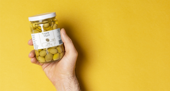 Green olives glass jar with blank label inside hand, editable PSD mock-up series with smart object layers template ready for your design